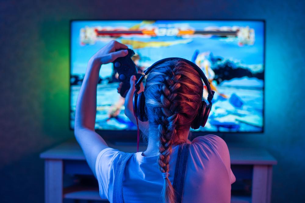 Mergina žaidžianti žaidimą